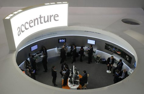 Visitors look at devices at Accenture stand at the Mobile World Congress in Barcelona, February 26, 2013. REUTERS/Albert Gea