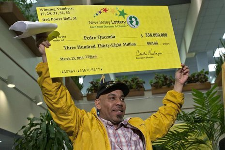 Pedro Quezada holds up the promotional Powerball jackpot check of $338 million at the end of a news conference at the New Jersey Lottery hea