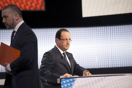 France's President Francois Hollande sits with his notes before appearing on France 2 television prime time news broadcast for an interview
