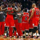 Luol Deng (arms raised) is hugged as he and his fellow Chicago Bulls players celebrate after beating the Miami Heat in an NBA basketball game at the United Center on March 27, 2013, 101-97. REUTERS/Jeff Haynes