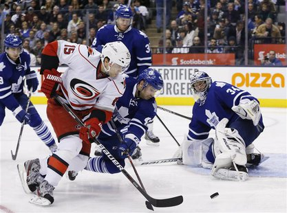 Toronto Maple Leafs goalie James Reimer (R) looks on with teammate Nazem Kadri (C) against Carolina Hurricanes Tuomo Ruutu during the third