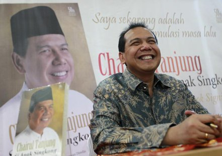 Founder and chairman CT Corp Chairul Tanjung smiles as his sits in front of his portrait at a book shop during his book launch in Jakarta Ju