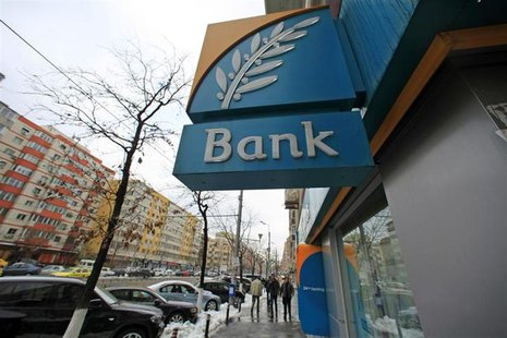 People walk past a branch of the Bank of Cyprus in Bucharest March 28, 2013. REUTERS/Radu Sigheti