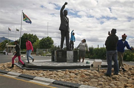 Visitors walk past a statue of former South African president Nelson Mandela outside the Victor Verster Prison near Paarl in the Cape winela
