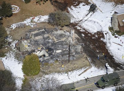 Authorities stand at the site of a burnt out cabin near Angelus Oaks, California February 13, 2013, where police believe they engaged in a s