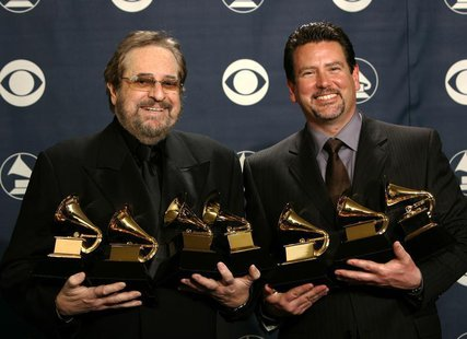 "Producers Phil Ramone and John Burk hold the awards won by Ray Charles and his album ""Genius Loves Company"" at the 47th annual Grammy Awards"