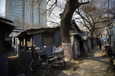 A man stands at an alley next to a residential compound in central Beijing, March 22, 2013. REUTERS/Petar Kujundzic