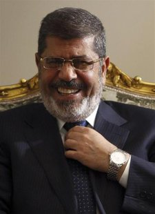 Egypt's President Mohamed Mursi laughs during his meeting with U.S. Secretary of State John Kerry (not pictured) at El-Thadiya presidential