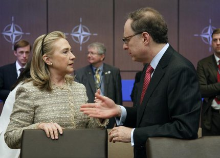 U.S. Secretary of State Hillary Clinton (L) talks to NATO Deputy Secretary General Alexander Vershbow before a Foreign Ministers meeting wit