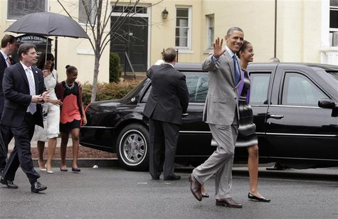 U.S. President Barack Obama waves as he walks with first lady Michelle Obama (L) and their daughters Malia (R) and Sasha after attending Eas