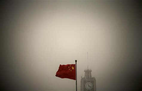 A Chinese national flag flies in front of Beijing Telegraph Building on a hazy morning in central Beijing in this February 28, 2013 file pho