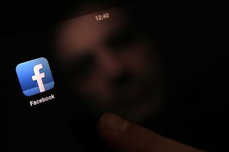 A man uses an iPad with a Facebook app in this photo illustration in Sofia January 30, 2013. REUTERS/Stoyan Nenov