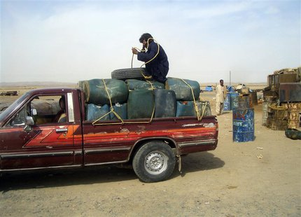 A man sits on top of plastic canisters of petrol that he says was brought from Iran, as he prepares to unload them from a van at a roadside