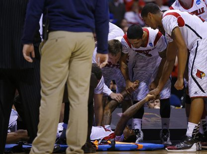 Louisville Cardinals players hold hands with Kevin Ware (5) after he broke his leg in the first half against the Duke Blue Devils during the