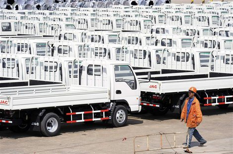 A worker walks past Chinese trucks for exporting at a port of Liangyungang, Jiangsu province, March 31, 2013. China's official manufacturing