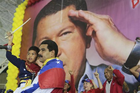 Venezuela's acting President Nicolas Maduro carries a child dressed as national hero Simon Bolivar in front of a poster of late president Hu