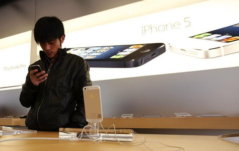 A visitor tries an iPhone at an Apple store in Beijing March 28, 2013. REUTERS/Kim Kyung-Hoon