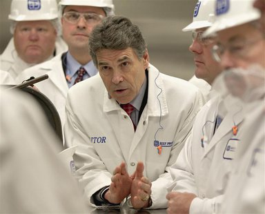 Texas Governor Rick Perry (C) asks a question with Iowa Governor Terry Branstad (R) and Nebraska Lt. Governor Rick Sheehy (2nd R) during a t