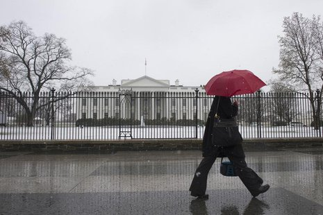 A pedestrian walks down Pennsylvania Avenue past the White House during an early spring snowstorm, in Washington March 25, 2013. REUTERS/Mar