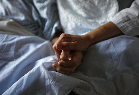 A woman holds the hand of her mother who is dying from cancer during her final hours at a palliative care hospital in Winnipeg July 24, 2010