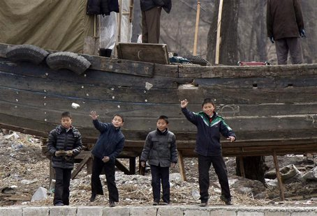 Children throw stones into Yalu River, at the river banks, near the North Korean town of Sinuiju, opposite the Chinese border city of Dandon