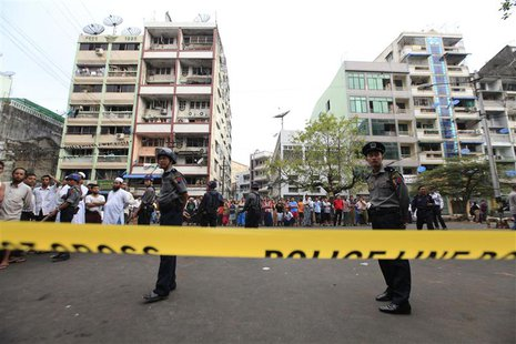 Police stand near a mosque and school dormitory that were damaged by a fire in Yangon April 2, 2013. REUTERS/Soe Zeya Tun