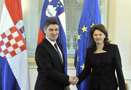Slovenian Prime Minister Alenka Bratusek (R) shakes hands with her Croatian counterpart Zoran Milanovic before the Slovenian parliament is e