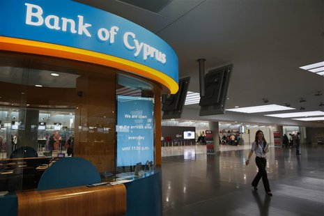 A woman working at Larnaca's airport walks past a small branch of the Bank of Cyprus inside the airport March 31, 2013. REUTERS/Yorgos Karah