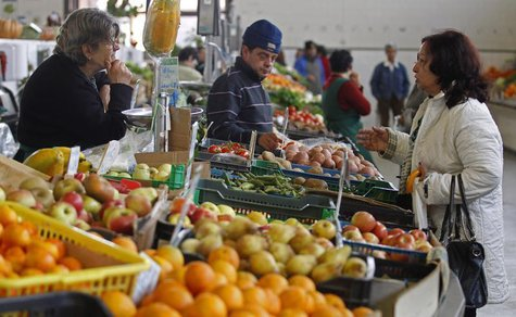People talk at the vegetable market in Olhao in the southern Portuguese province of Algarve March 12, 2013. REUTERS/Jose Manuel Ribeiro