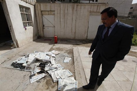 An Iraqi journalist walks past the archive newspapers burned after attack by an armed group at the newspaper's headquarters of Addustour new