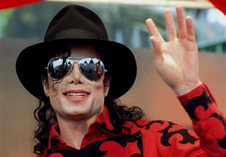 Michael Jackson waves to the crowd, numbering a few thousand, gathered in front of the Sydney Opera House in this November 17, 1996 file pho