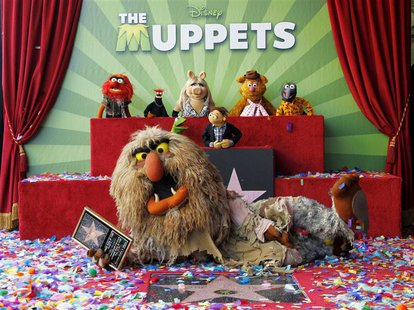 Muppet character Sweetums holds a commemorative plaque as he lies beside the newly unveiled Muppets star as other Mupetts background (L-R) A