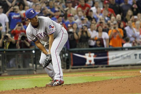 Texas Rangers pitcher Yu Darvish watches after a hit by Houston Astros' Marwin Gonzalez goes through his legs and he lost his perfect game w