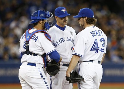 Toronto Blue Jays pitching coach Pete Walker (C) talks with starting pitcher R.A. Dickey and catcher J.P. Arencibia during the sixth inning