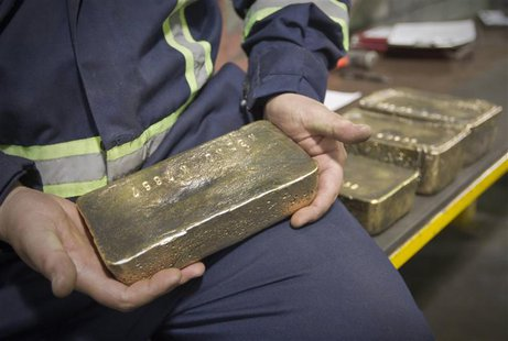 A worker holds a polished gold alloy bar in a workshop at Kumtor gold mine extraction factory in the Tien Shan mountains, some 350 kilometre