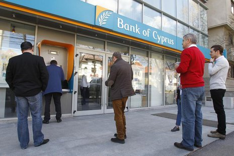 People wait in front of a branch of Bank of Cyprus to withdraw money from its ATM in Bucharest April 1, 2013. REUTERS/Bogdan Cristel