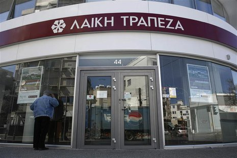 A man tries to look inside a branch of Laiki Bank a few hours before the re-opening of the banks on the island in Nicosia in this March 28,