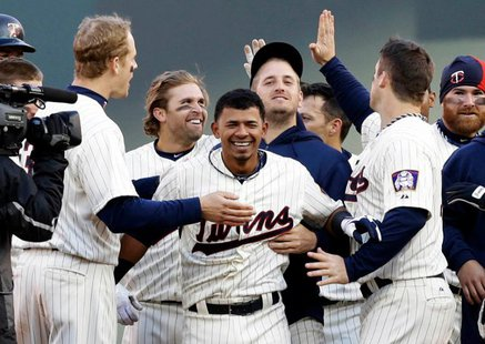 Minnesota Twins shortstop Eduardo Escobar (c) is congratulated by teammates Justin Morneau (l), Joe Mauer (r) and others following his game-winning, two-run double in the ninth inning of a 3-2 victory over visiting Detroit at Target Field in Minneapolis on Apr. 3, 2013. (photo courtesy Minnesota Twins)