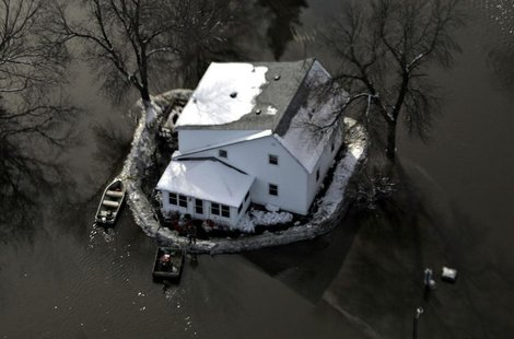 An aerial view shows a house with a sandbag levee is surrounded by floodwaters south of Fargo, North Dakota in this file photo taken March 2