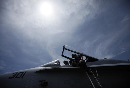 Crew members work on the cockpit of a F/A-18C fighter jet on the deck of the USS Ronald Reagan (CVN76) in Hong Kong August 12, 2011. REUTERS