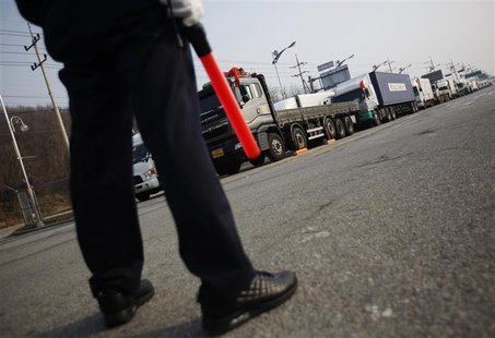 A South Korean security guard keeps watch as South Korean trucks wait to enter the Kaesong industrial complex in North Korea, at the South's