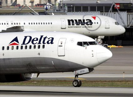 A Delta Air Lines jet takes off past a Northwest Airline jets parked at gates at the Minneapolis St.Paul International Airport in Minneapoli