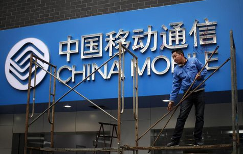 A labourer works in front of a sign for China Mobile at the company's office in downtown Shanghai March 11, 2013. REUTERS/Carlos Barria