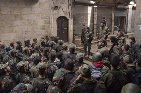 Forces loyal to Syria's President Bashar al-Assad get briefed before being deployed from the al-Sabaa Bahrat district to the old souk of Ale