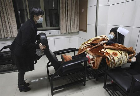 A patient with fever (R) is accompanied by a family member while receiving treatment at the hospital where a 67-year-old H7N9 patient is bei