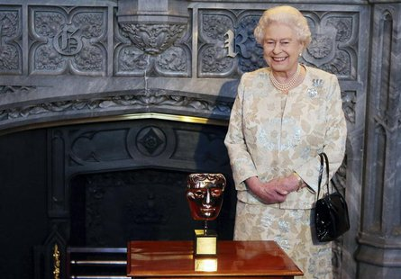Britain's Queen Elizabeth poses with her honorary British Academy of Film and Arts (BAFTA) award, after receiving it from actor Kenneth Bran