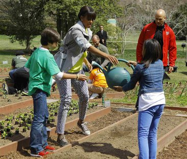 U.S. first lady Michelle Obama (C) and school children Ariana Docanto (R) and Emilio Vega (L) water wheat they have just planted at the fift