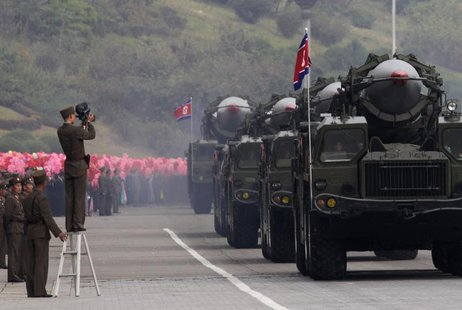 A North Korean soldier films military vehicles carrying missiles during a parade to commemorate the 65th anniversary of founding of the Work