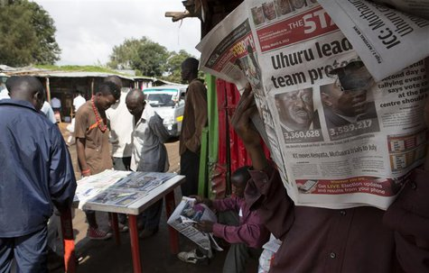 A man reads the morning edition of The Standard newspaper showing provisional results for the two main presidential election contenders in t