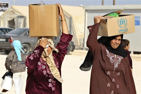 Syrian refugees carry aid and ration at the Zaatari refugee camp in the Jordanian city of Mafraq, near the border with Syria October 22, 201